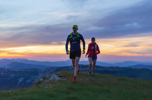 Two athletes trail running in the hills during sunset.