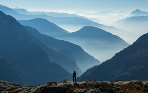 Man looking at the foggy, blue layers of mountains. Near Chamonix, France.