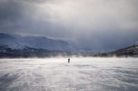 Cross country skier with sled (pulka) on a frozen river in in national park Sarek. Lapland, Sweden.