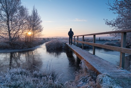 Man walking over a small footbridge in the frozen, Dutch countryside during a winters dawn.