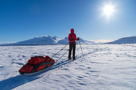 Female cross country skier with sled (pulka) on a lake enjoying the view at the Ahkka mountain.