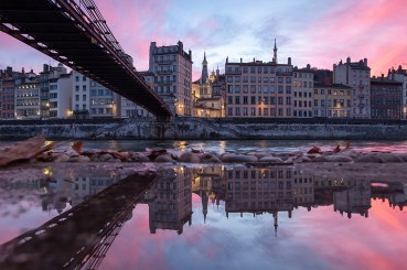 Footbridge Passerelle Saint-Vincent reflected in a puddle during a pink sunset in Vieux-Lyon.