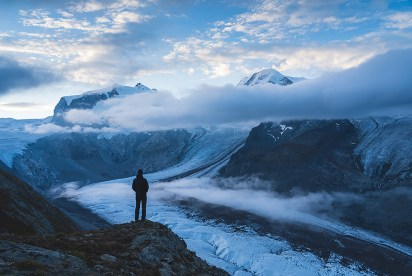 A man looking at the mountains near Zermatt, Switzerland, on a cloudy morning.