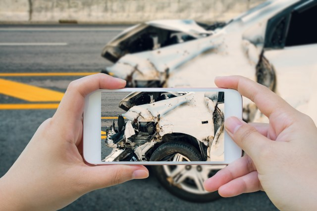 North Dakota - accident law firm - woman using smartphone take photo of car crash accident on the road