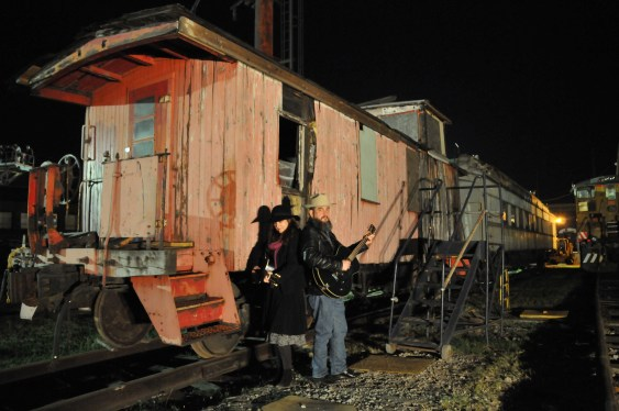 Quinn Sands and Richard Hearn standing in front of an old abandoned Caboose