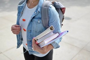 student carrying a backpack and books