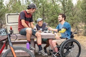 Young man in wheelchair shares beers with man and woman at picnic table