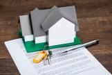 House model and keys on top of document