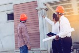 photo of home inspectors wearing orange hard hat