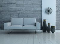 gray wall panelling with a gray couch and three big vases