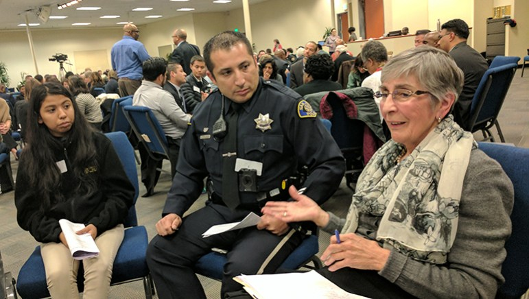 Officer Jose Montoya (center) listens as Carmen Johnson (right) talks about a negative interaction she had with a San Jose cop. (Photo by Jennifer Wadsworth)