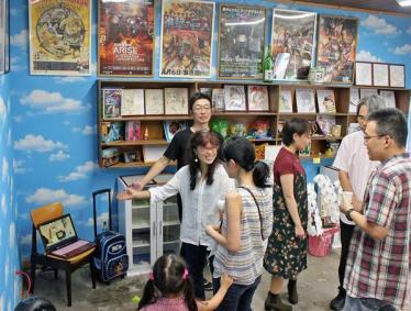 訪れたアニメファンらを案内する小林美代子さん(左中央)=総社市