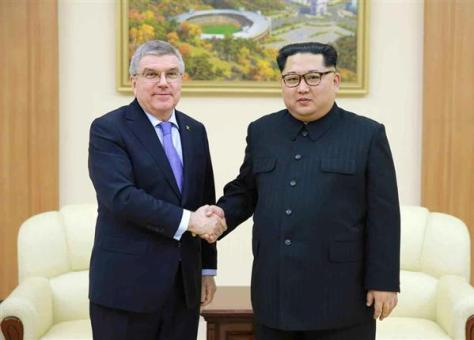 IOCのバッハ会長(左)と北朝鮮の金正恩朝鮮労働党委員長。労働新聞が31日掲載した=30日、平壌(コリアメディア提供・共同)