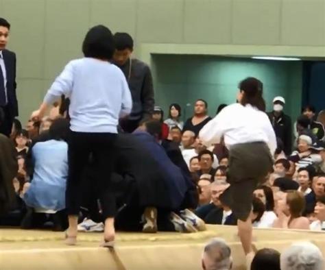 動画投稿サイト「ユーチューブ」に4日投稿された、京都府舞鶴市の大相撲春巡業で多々見良三市長が倒れた際、土俵に上がる女性(手前)の映像