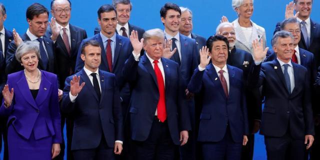 30日、手を振って撮影に応じる安倍晋三首相(前列右から2人目)、トランプ米大統領(同3人目)ら各国首脳=ブエノスアイレス(ロイター)