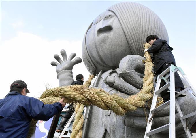 巨大しめ飾りが取り付けられる「ゲゲゲの鬼太郎」の石像=25日、鳥取県境港市