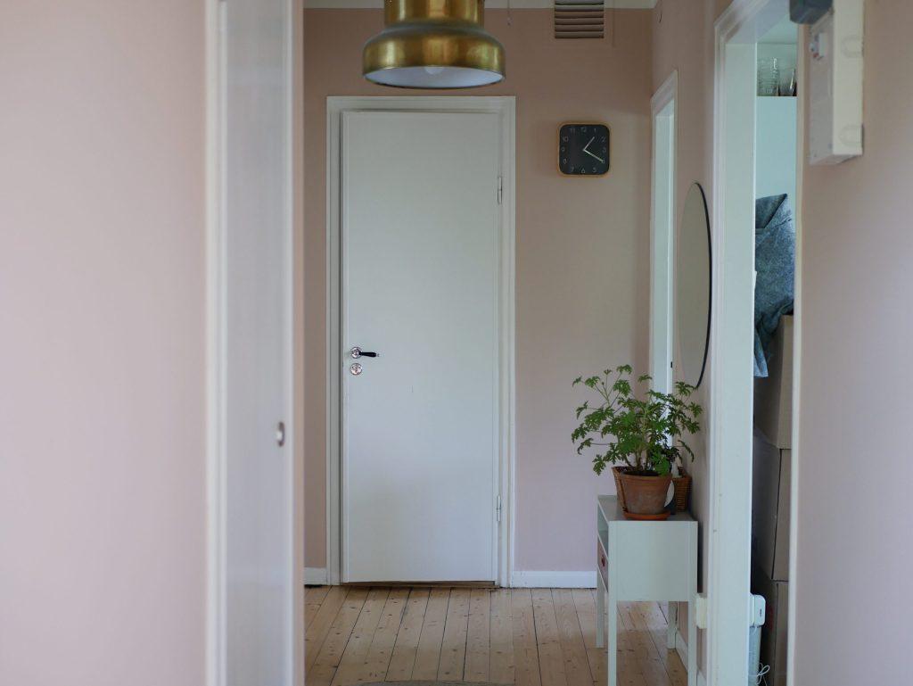 En hall med nymålade, rosa väggar och trägolv