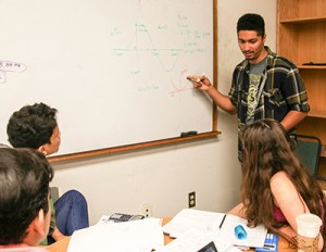 Ian Weaver (at white board) works with ACE students in a physics problem-solving session. Now a senior in astrophysics, Weaver joined the ACE Program his freshman year and has been on the student staff since he was a sophomore. (Credit: C. Lagattuta)