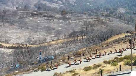 Cal Fire bravely walking toward the burn. PG&E is fixing the pole behind them.