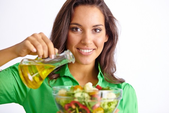 Femme prenant de l'huile d'olive dans son alimentation