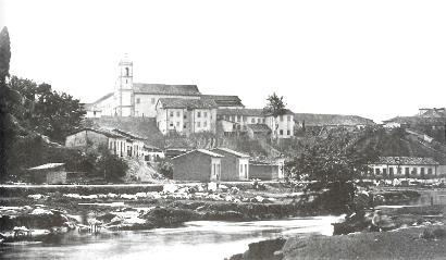O Rio Tamanduateí correndo ao lado da Rua 25 de Março; ao fundo, o mosteiro de São Bento. Foto de Militão Augusto de Azevedo, em 1862.