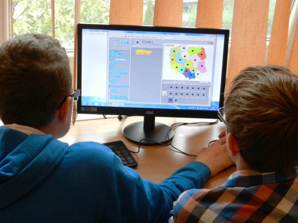 Due bambini davanti al display di un computer