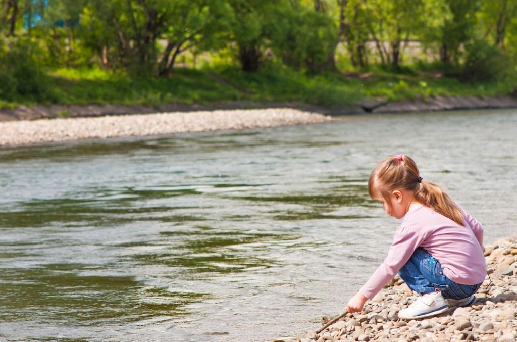 Una bambina gioca in riva al fiume