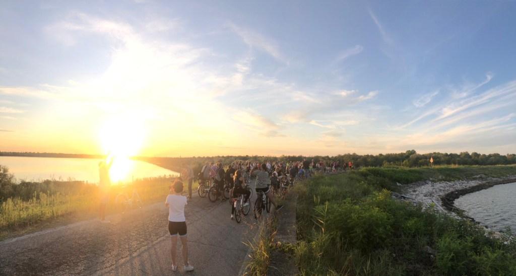 Un gruppo di persone attraversano in bicicletta il Parco del Delta del Po al tramonto