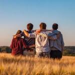 Un gruppo di adolescenti di spalle, abbracciati in un campo di grano