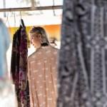 Una ragazza cerca abiti usati in una rivendita