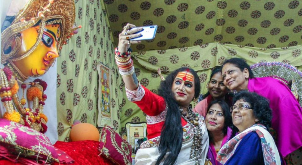 Laxmi Narayan Tripathi, high priestess of a convent of hijras, takes selfies with admirers at India's 2019 Kumbh Mela religious festival.