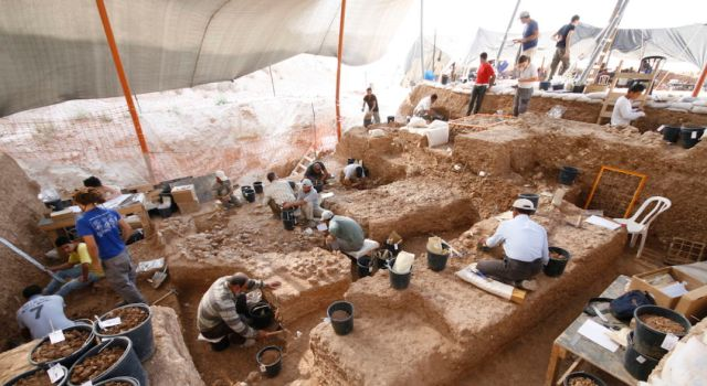 Several people dig and sift through brown dirt, surrounded by black buckets and tools.