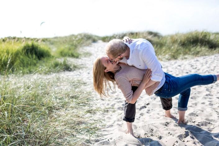Mann umarmt Frau und kuss Strand Düne Laboe Paarshooting