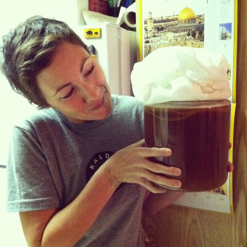 Sarah holds Kombucha Tea with floating SCOBY and foam