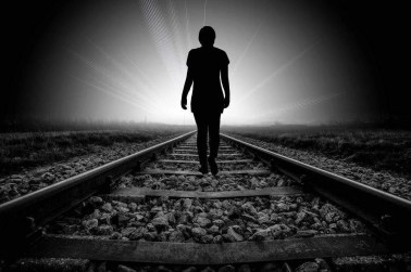 Silhouette walking down a railroad track toward a light. The angel number 0 means that even when we feel alone we are never really alone.