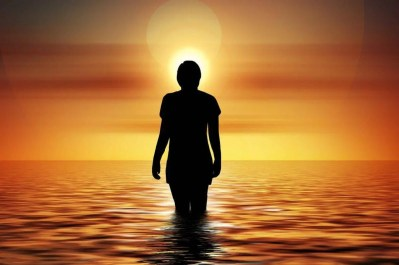 Those who see Angel Number 1010 are experiencing and expansion of consciousness. This image has the silhouette of a person standing in the ocean at sunset with their head illuminated by the sun.