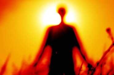 Blurred image of a person standing in front of the sun representing spirit guides being crossed over loved ones.