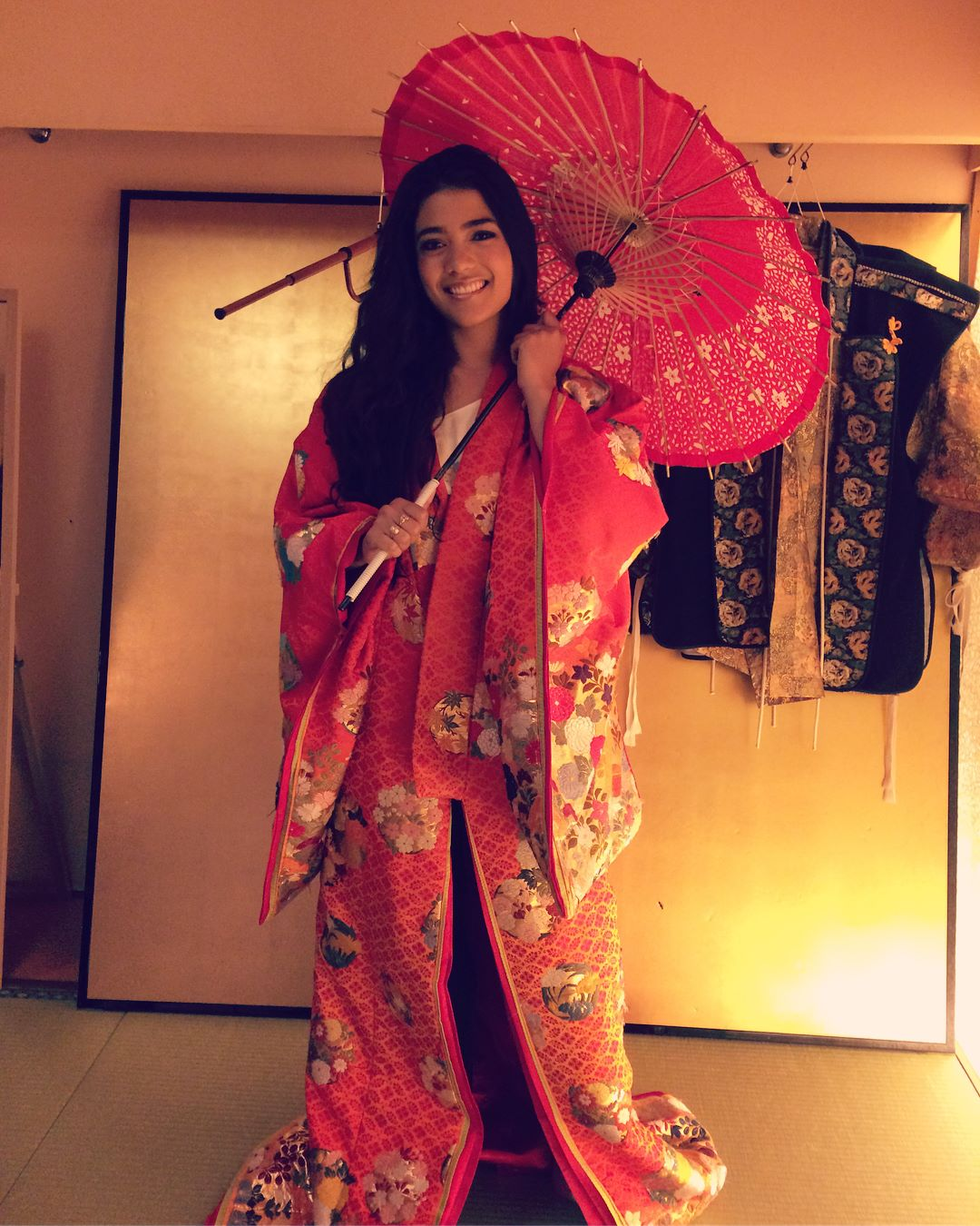 Girl wearing a red, floral kimono at the Samurai Museum in Tokyo