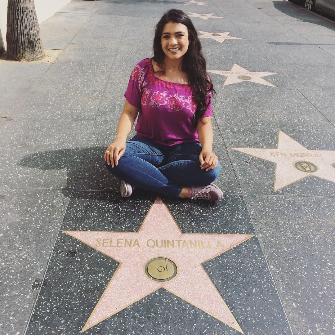 girl sitting at Selena Quintanilla's star, Hollywood Walk of Fame, L.A.
