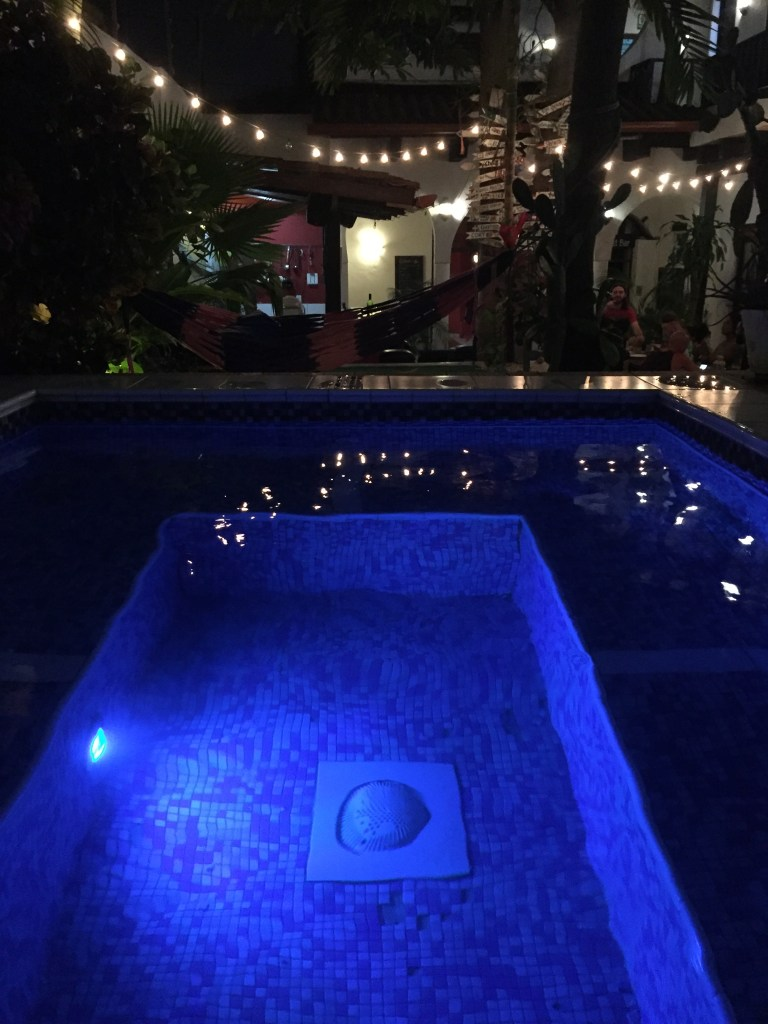 pool at hostel in courtyard with string lights at night
