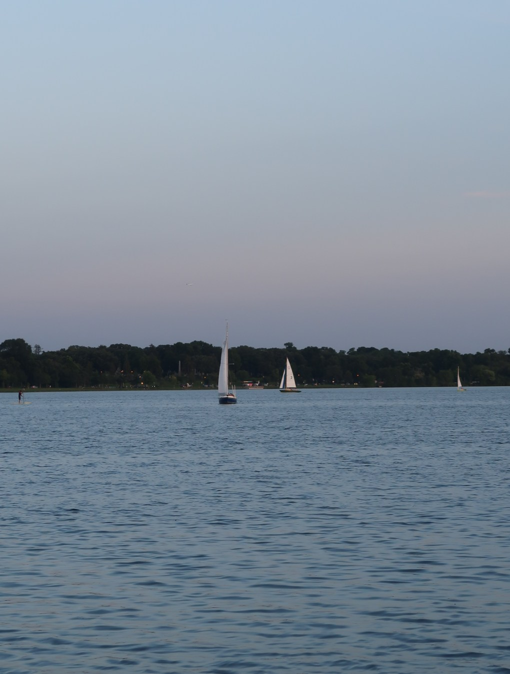 sunset on lake with sailboats in the distance
