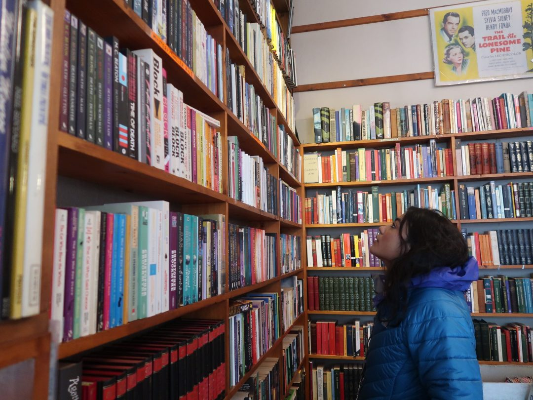 girl in blue coat looking at bookshelf in a book store