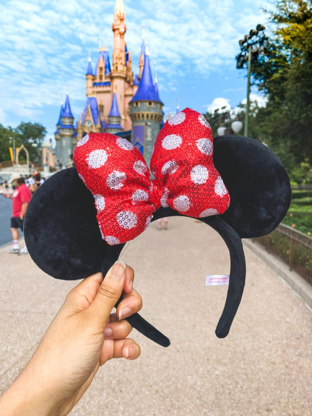 Minnie Mouse ear headband with red polka dotted bow and pink castle in background