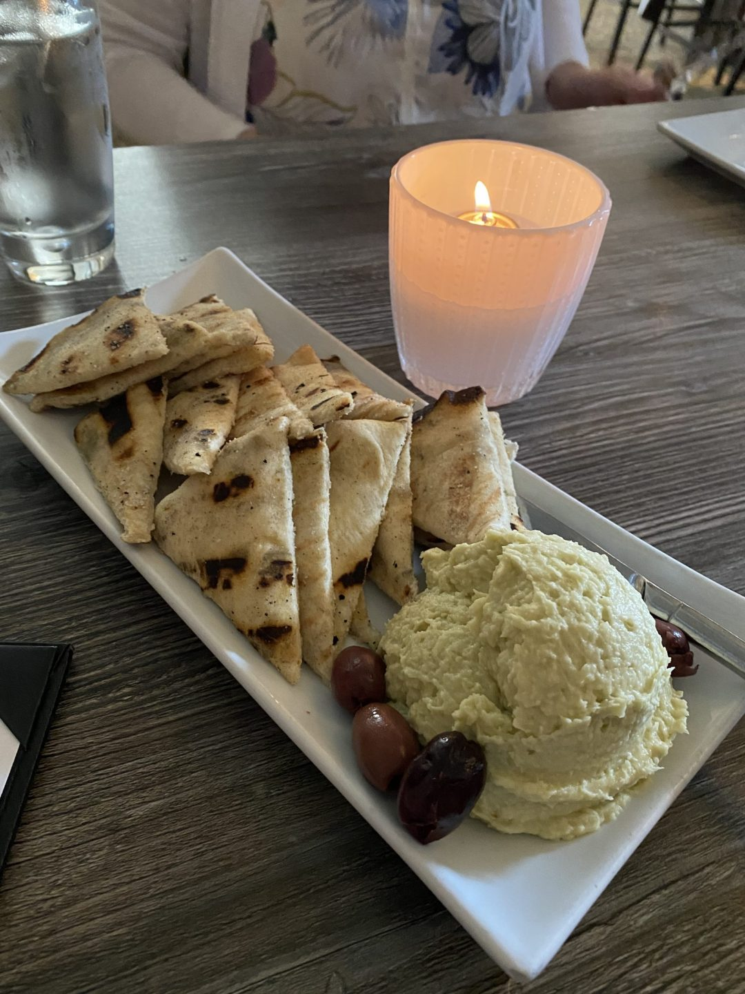 Hummus with pita and olives and a candle in the background