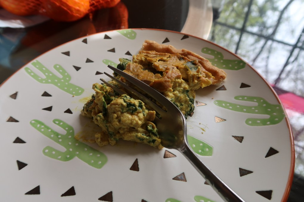 slice of vegan quiche on cactus plate and glass table