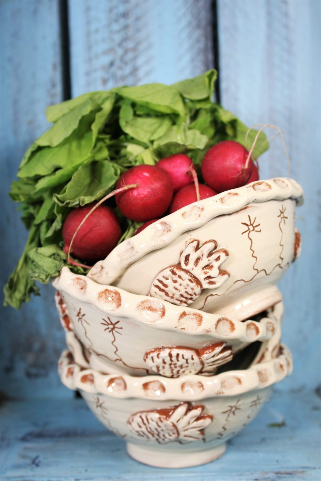 a stack of three slipware bowls in white and terracotta slipware with some fresh radishes