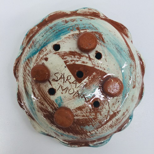 the bottom of a crcular soap dish signed by sarah monk artists signature studio pottery