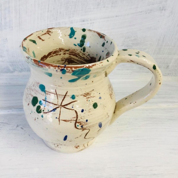 cream slipware mug with splatters of colour and a sgraffito daisy by sarah monk ceramics