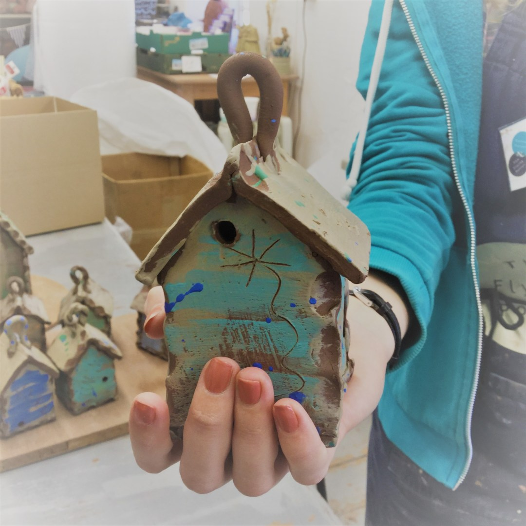 holding a wet clay slipware bug house in the studio of sarah monk ceramics