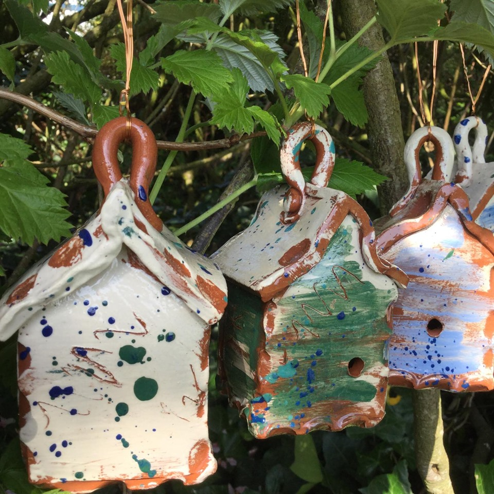 close up of three sarah monk ceramic bug houses hanging in the garden with leaves behind